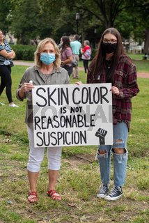 Two women hold an anti-racism protest sign