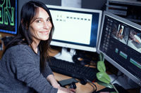A Young Dark-haired Female Video Maker Smiles While Working At Computer In A Photo Studio