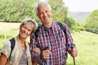 Zwei Senioren lächeln draußen im Sommer
