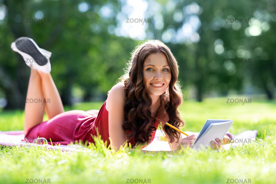 happy woman with diary or notebook at park