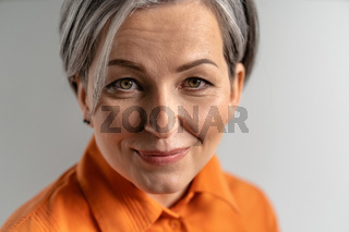 Close up portrait of a happy mature grey haired woman wearing orange shirt looking at camera. Pretty mid aged grey haired woman in orange shirt isolated on grey background