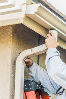 Worker Attaching Aluminum Rain Gutter and Down Spout to Fascia of House