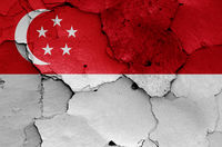 flags of Singapore and Indonesia painted on cracked wall