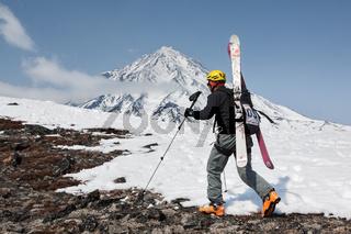 Ski mountaineer climbing on mountain on background volcano