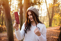 Young beautiful smiling caucasian woman taking selfie on cellphone in autumn park. A good sunny day and relaxation in nature creates a great mood