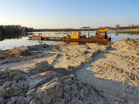 excavation machine at earthmoving work in sand quarry. Extraction of sand from a lake.