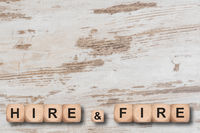 hire and fire printed on wooden cubes