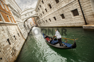 Gondola with gondolier and tourists on the canal in the Venice