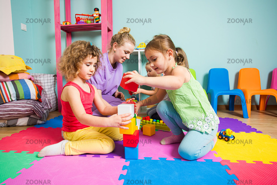 The group of girls in the kindergarten are playing with toys