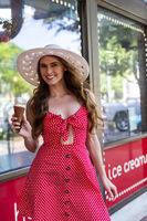 Lovely Brunette Model Eating Ice Cream While Posing Outdoors