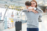 Paar in Fernbeziehung bei Umarmung am Flughafen