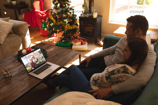 Couple sitting on couch having a videocall with man and son in santa hats waving on laptop at home