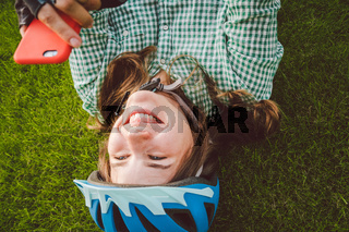 theme sport and technology. Beautiful caucasian woman student with toothy smile lies back rest green grass in bicycle helmet head hand mobile phone red case writes sms, prints message using internet