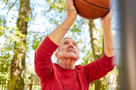konzentrierter Senior mit Ball beim Basketball