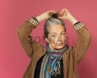 Mature gray-haired woman doing hairstyle. Creative Caucasian woman wearing casual clothes posing in studio on pink background
