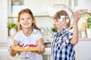Kinder präsentieren Obstkuchen in Küche