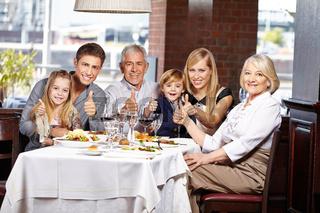 Familie im Restaurant hält Daumen hoch