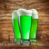 Alcoholic green beer in the glasses on a blurred wooden.