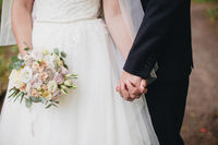Bride in white dress holds wedding bouquet. Groom hugs bride. Blurred background