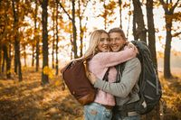 Young Cheerful Couple hugging In Autumn Forest