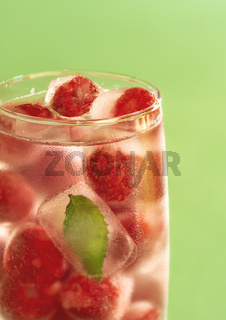 Glass of water with frozen raspberries. Cold drink.