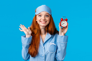 Cheerful and enthusiastic redhead girl dont want to oversleep, set alarm clock, holding red watch and smiling joyfully, waking up early for university exam, standing in nightwear blue background