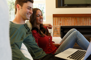 Caucasian couple having video call smiling to laptop sitting in living room