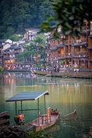 Old boat and historic wooden Diaojiao houses in Fenghuang