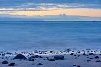 The sea after sundown and pebble beach at dawn
