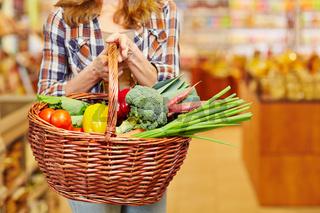 Frau trägt Korb voller Gemüse im Supermarkt