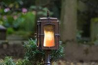 Grablaterne mit brennender Kerze auf einem Friedhof