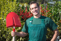 Farmer or gardener posing with shovel in garden