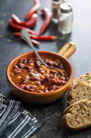 Chili con carne. Mexican food with beans in pot and bread.