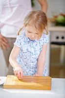 Kind schlägt Ei auf in der Küche