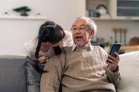 elderly man with granddaughter using tablet together