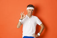 Concept of sport, fitness and lifestyle. Portrait of confident middle-aged sportsman, showing okay sign and look pleased, guarantee something or recommending gym, orange background