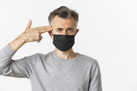 Concept of covid-19, social distancing and quarantine. Close-up of sad middle-aged man in black medical mask, pointing finger gun at head and looking distressed, standing over white background