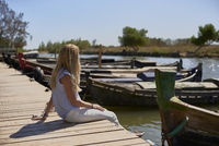 Blonde girl sitting on a jetty