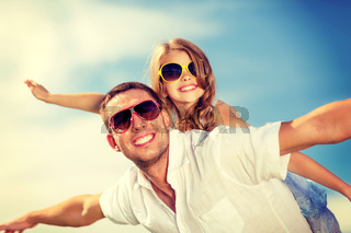 happy father and child in sunglasses over blue sky