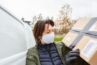 Lieferservice Paketbotin mit Mundschutz prüft Paket