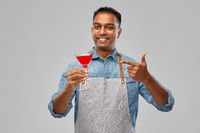 indian barman in apron with glass of cocktail