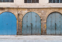 Closed blue weathered wooden arched doors in stone bricks wall, located in old abandoned district