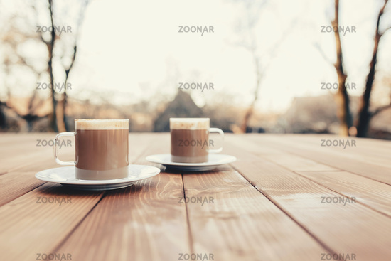Two cups of coffee in the wooden brown terrace background