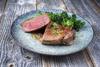 Traditional barbecue dry aged sliced wagyu sirloin beef steak with kalette and herbs as closeup on modern design plate on a wooden board