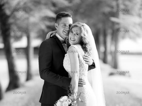 Bride and groom hugging tenderly posing during photo shooting in park.