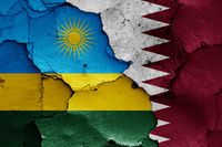 flags of Rwanda and Qatar painted on cracked wall