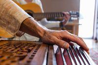 Senior man hands playing harmonium
