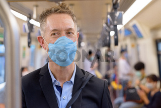 Face of mature businessman with mask standing with distance inside the train