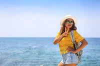 Female tourist wanderlust with backpack wearing sunglasses and straw hat