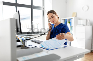 doctor with computer calling on phone at hospital